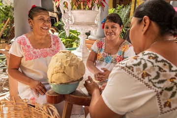 Women making Tortillas. Group of smiling cooks preparing flat bread tortillas in Yucatan, Mexico Wall mural