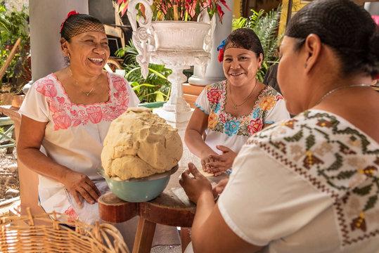 Women making Tortillas. Group of smiling cooks preparing flat bread tortillas in Yucatan, Mexico