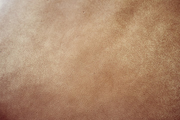 Elegant light brown leatherette background with vignetting.