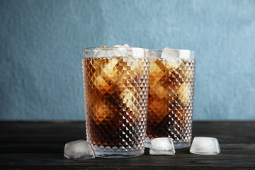 Glasses of refreshing cola with ice cubes on table
