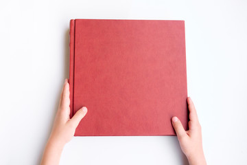 Kid holding red leather covered photobook or album. Photobook lie on white background.