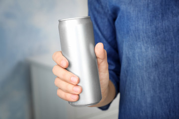 Woman holding aluminum can with beverage on blurred background, closeup. Space for design