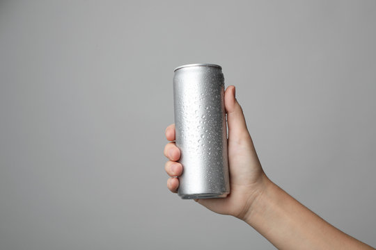 Woman holding aluminum can with beverage on grey background, closeup. Space for design