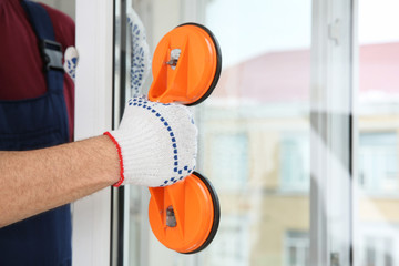 Construction worker using suction lifter during window installation indoors, closeup