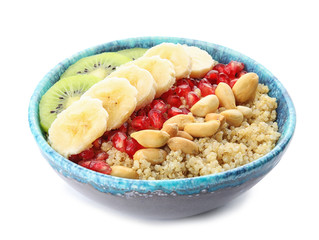 Bowl of quinoa porridge with peanuts, kiwi, banana and pomegranate seeds on white background