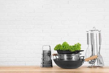 Set of clean cookware, utensils and lettuce on table against  white brick wall. Space for text