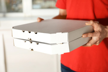 Young man with pizza boxes indoors, closeup. Food delivery service