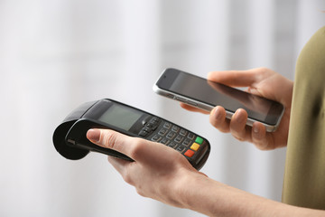 Woman using modern payment terminal with mobile phone indoors, closeup