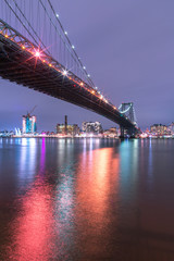 View on Williamsburg bridge from east river at night with long exposure