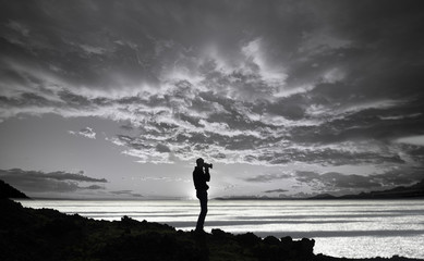 silhouette of a photographer on the top of a cliff in a  cloudy sunset.