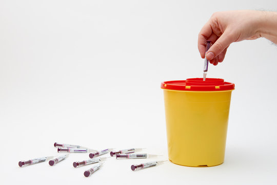 Hand putting needle in safety yellow bin over white background