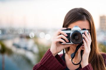 Pretty woman taking photos with retro camera