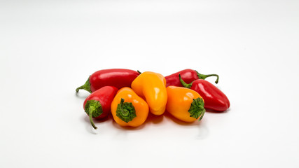 a group of red and orange mini sweet peppers isolated on white