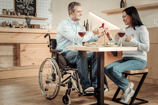 Smiling man in wheelchair making a surprise to woman