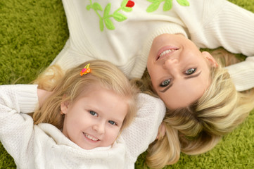 mother with little daughter lying on green carpet