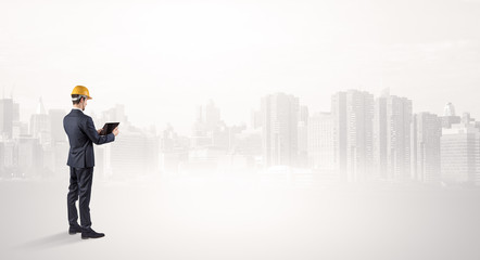 Young supervisor architect standing and looking at a big city panorama