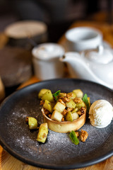 English apple crumble with nuts, mint and ice cream ball