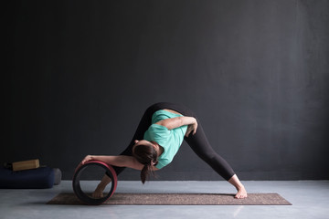 Woman doing yoga asana Wide Legged Forward Bend using special wheel.