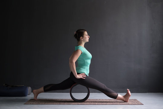 Young woman doing yoga or pilates exercise. Splits, hanumanasana using wheel