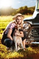 Woman with labrador in the front of a car