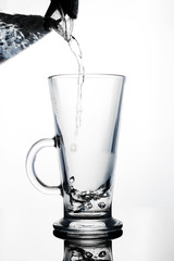 Hand pours water into a glass glass Cup of glass teapot. Shut. Isolated on white background