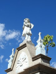 Scene in a graveyard: bottom view of a stone statue of an angel with hands clasped, praying. It is on the top of a mausoleum. Blue sky with few clouds on a sunny day.