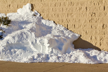 Remnants of a snowdrift against a light brown brick wall building