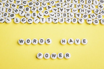 The expression WORDS HAVE POWER made of white plastic blocks on yellow background with many letters on the top