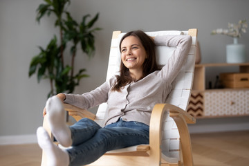 Happy calm young woman relaxing on comfortable wooden rocking chair in living room, smiling...