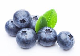 Fresh raw organic blueberries with leaf on white background. Macro close up