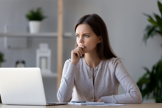 Thoughtful puzzled female student worker looking away pondering thinking solving problem at work, anxious pensive young woman concerned make difficult decision feeling lack of ideas creativity crisis