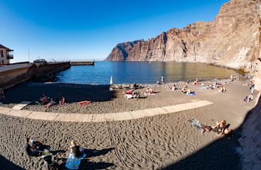 People in summer holiday on Playa de los Guios near Los Gigantes mountain in Tenerife island, Spain