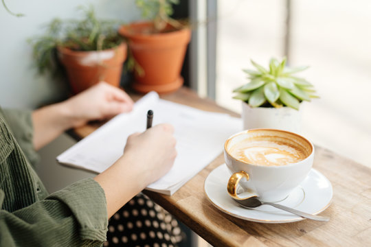 Woman sit at office surround with green plants, coffee and write at her note book