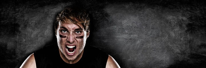 American football player screaming on black chalkboard texture background copy space for advertising. Panoramic banner blackboard with man athlete ready to play face paint black eye.