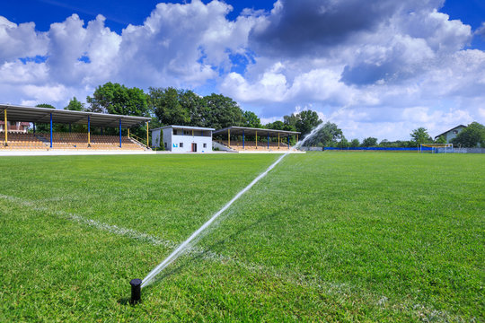 Automatic lawn grass watering system at the stadium. A football, soccer field in a small provincial town. Underground sprinklers spray jets water.
