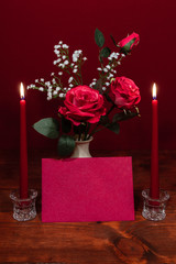 Beautiful pink roses in a vase accented with Baby's Breath flowers, Two lit ed candles in crystal holder and a card