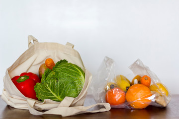 Eco reusable bag with vegetables and plastic bag with fruits.