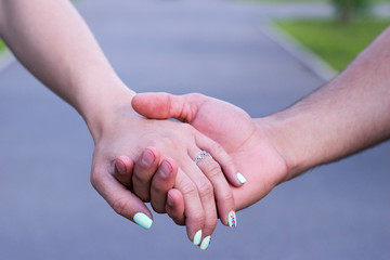 Close up of couple in love holding each other hands