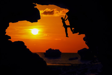 Photographer climbing rock in the cave near the beach at red sky sunset.