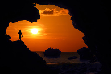 Photographer standing in the cave near the beach at red sky sunset.