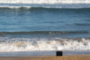 Focus on camera taking video or timelapse footage from sandy beach towards rolling surf and waves