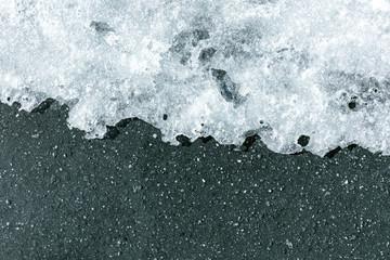 melting ice on asphalt in the spring. melting snow natural background