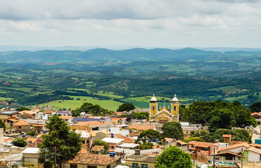 Panoramic view of São Thomé das Letras' downtown, with historical church in foreground and Minas Gerais' hilly landscape on background. Brazil.