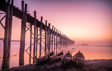 The U Bein Bridge in Mandalay, Myanmar is a old biggest wooden bridge of the world and wooden boats with twilight sky background