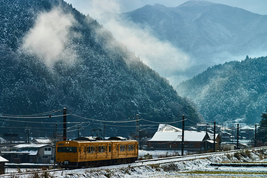 A Japanese train running in the snowy rural area