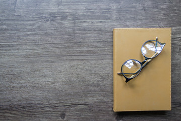 Glasses and gold notebook on wooden table, Copy space.