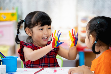 Asian cute kid girl showing hand with colorful painting. creative girl with fun.