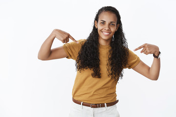 Charming friendly-looking kind and timid african-american feminine woman with curly long hair bending as pointing at herself as smiling, volunteering, wanting participate, be candidate over gray wall