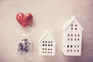 A jar of heart tree growing on money coins and model houses, social responsibility, homeless shelter and donation concept