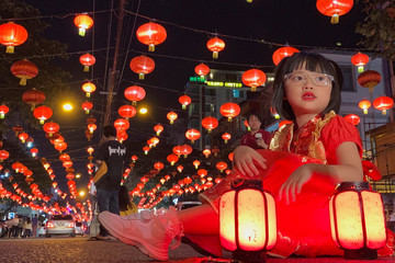 A girl poses for a Lunar New Year picture in the street in Chinatown, Yangon